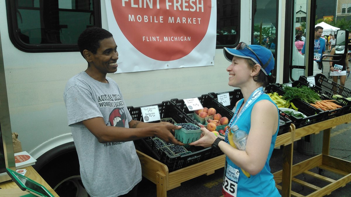 A runner purchases produce from the Flint Fresh Mobile Market (Community Foundation of Greater Flint)